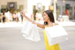 Shopping woman in New York City looking for taxi. Shopping woman in New York City looking for yellow taxi cab. Beautiful happy summer shopper holding shopping Royalty Free Stock Images