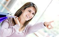 Shopping woman pointing away Stock Photo