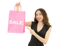 Shopping woman pointing to sale sign on a paper shopping bag Stock Images
