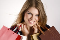 Shopping woman. Portrait of glamorous spree female shopper holding shopping bags. Nice smiling Caucasian blue eyed woman looking at the camera Stock Photography