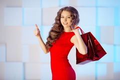Shopping woman with red bags, presents in mall. shopping center. Stock Photography