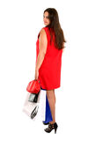 Shopping woman in red dress turn back. Shopping woman in red dress with bags turn back Royalty Free Stock Photo
