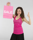 Shopping woman with a sale shopping bag thumbs up Stock Images