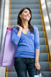 Shopping woman on scalators Stock Image