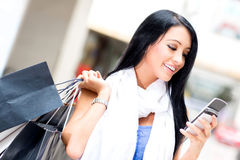 Shopping woman sending a text Royalty Free Stock Photos