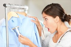 Shopping woman shocked. Over price tag. Funny shopper woman staring amazed at price. Mixed race Caucasian / Asian Chinese young female model in clothing shop royalty free stock photo