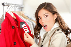 Shopping woman shocked over price. Shopping woman shocked and surprised over price looking at price tag on coat or jacket. Woman shopper shopping for clothes Royalty Free Stock Images