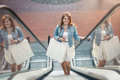 Shopping woman in shopping mall on escalator Royalty Free Stock Photography