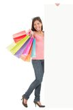 Shopping woman with sign. Shopping woman showing commercial sign. Full length picture of a beautiful young mixed race woman holding a blank billboard sign while Stock Photos