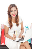 Shopping woman sitting with laptop and holding credit card Royalty Free Stock Images