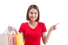 Shopping woman smiling joyful and happy holding shopping bags pointing Stock Photo