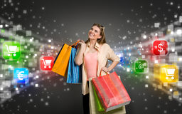 Shopping woman surrounded by icons of e-commerce. Happy shopping woman surrounded by glow icons of e-commerce Royalty Free Stock Photos