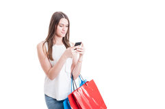 Shopping woman texting on her mobile phone and holding bags Royalty Free Stock Images