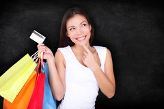 Shopping woman thinking with bags on blackboard. Background. Shopper girl holding credit card and shopping bag looking up at blackboard / chalkboard background royalty free stock images