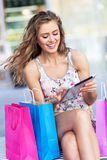 Shopping woman using digital tablet Stock Photography