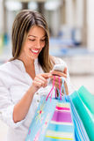 Shopping woman using smart phone Royalty Free Stock Image