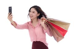 Shopping woman using smartphone to taking a selfie isolated on w. Shopping woman using smartphone to taking a selfie isolated on a white background royalty free stock image