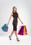 Shopping woman walking with bags  on white background. Royalty Free Stock Photo