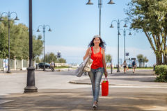 Shopping woman walking though avenues. Attractive mature woman walks through the avenues of Rimini while doing shopping Royalty Free Stock Images