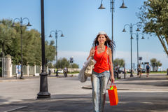 Shopping woman walking though avenues. Attractive mature woman walks through the avenues of Rimini while doing shopping Stock Photo