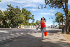 Shopping woman walking though avenues. Attractive mature woman walks through the avenues of Rimini while doing shopping Royalty Free Stock Image