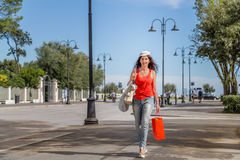 Shopping woman walking though avenues. Attractive mature woman walks through the avenues of Rimini while doing shopping Stock Photography