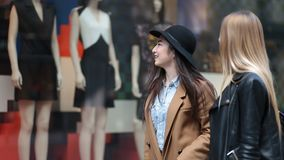 Shopping women looking at clothing store window. Shopping young women looking at clothing store window outside shop. Multiethnic girlfriends standing in front of stock video footage