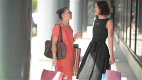 Shopping women talking happy holding shopping bags having fun laughing. Two beautiful young woman girlfriends on travel. Vacation, good mood stock video