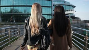 Shopping women walking on pedestrian bridge. Back view of two attractive long-haired women with shopping bags, holding hands walking on pedestrian bridge at stock video