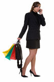 Shopping after work. Full body of a happy woman holding up a bunch of colorful shopping bags still wearing business suit and carrying briefcase with one leg up Stock Photo