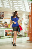 Shopping, Young beautiful woman on the background showcases a shoe store Stock Image