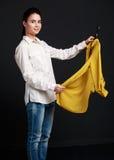 Shopping. Young brunette woman choosing a shirt Stock Image