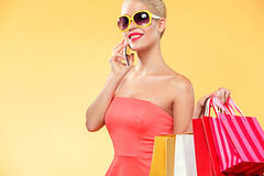 Shopping. Young smiling woman holding bag and mobile phone make her thumb up in black friday holiday. Girl on yellow Stock Photography