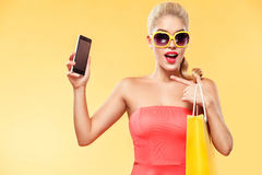 Shopping. Young smiling woman holding bag and mobile phone make her thumb up in black friday holiday. Girl on yellow stock photos