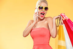 Shopping. Young smiling woman holding bag and mobile phone make her thumb up in black friday holiday. Girl on yellow Royalty Free Stock Image