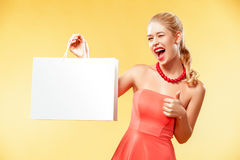 Shopping. Young smiling woman showing sale bag make her thumb up in black friday holiday. Girl on yellow background with stock photography