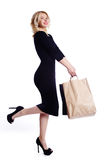 Shopping young woman holding bags isolated on white studio background. Love fashion and sales. Happy blond girl in black luxury gl Stock Photography