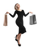 Shopping young woman holding bags isolated on white studio background. Love fashion and sales. Happy blond girl in black luxury gl Stock Image