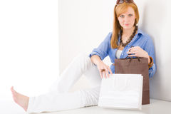 Shopping young woman with paper bag sitting Royalty Free Stock Photography