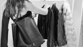 Shopping. Young woman tries on the leather jacket stock video footage