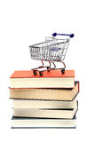 Shoppingcart on top of books Stock Photo