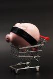 Shoppingkorg med den rosa spargrisen med inre anseende för svartögonbindel på svart bakgrund Royaltyfri Bild