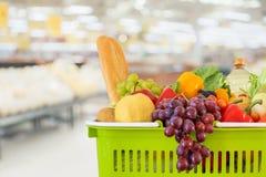 Shoppingkorgen som fylldes med frukter och grönsaker med supermarketlivsmedelsbutiken, gjorde suddig defocused bakgrund royaltyfri fotografi