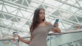 Shoppingkvinna som ler med påsar som talar på telefonen i galleria Härlig flicka med smartphonen i köpcentrum eller lager videofilmer