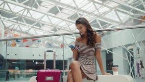 Shoppingkvinna som ler med påsar som talar på telefonen i galleria Härlig flicka med smartphonen i köpcentrumbagage lager videofilmer