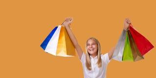 Shoppingkvinna som rymmer shoppingpåsar ovanför hennes huvud som ler under försäljningsshopping över gul bakgrund arkivbilder