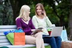 Shoppingkvinnor som använder den Digital minnestavlan och mobiltelefonen Arkivbilder