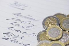 Shoppinglistan med en euro coins Royaltyfri Fotografi