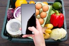 Shoppinglivsmedel för ung kvinna på online-supermarket med hennes mobiltelefon Ask av livsmedelsbutikmat och från lager på bakgru arkivbild