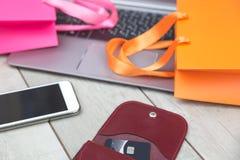 Shoppingpåsar, kreditkort, bärbar dator på skrivbordet arkivbild
